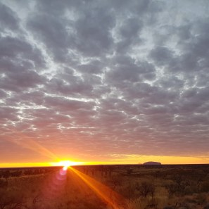 Sun rising to the left of Uluru